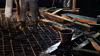 Pouring concrete mix from cement pump up at night