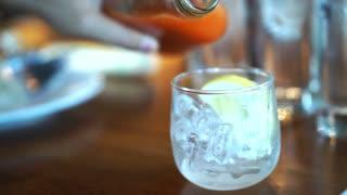 Pouring orange juice lemon mocktail in to ice glass in restaurant