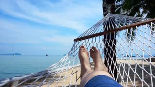 POV of Feet swinging in a hammock on coconut tree. Relaxing on the beach of Thailand