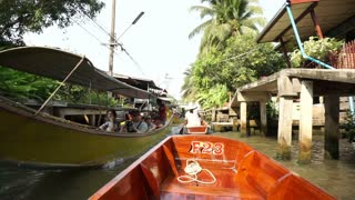 POV of tourist, point of view boat ride through a floating boat market in Thailand