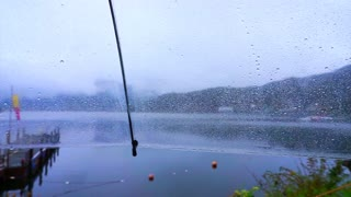 POV point of view sitting alone at lake on the rainy day. Clear umbrella and raindrops dripping. Abstract sad and lonely