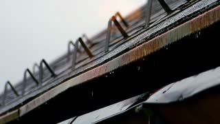 Rain dropping and dripping on house roof and gutter