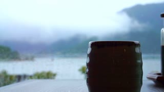 Relaxing drinking Japanese hot tea in front of Fuji mountain lake. Slow life, connect with nature zen style