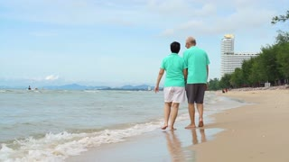 Retired Asian Senior Couple walking on tropical beach morning with beautiful sky