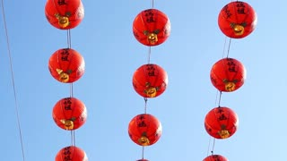 Row of red Chinese paper lanterns with ornate gold patterns and tassels. hanging on wires outside. Shot on the sky background at Buddhist temple.