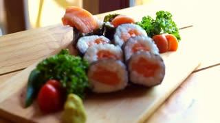 Salmon nori maki sushi beautiful display on wooden board. Japanese cuisine