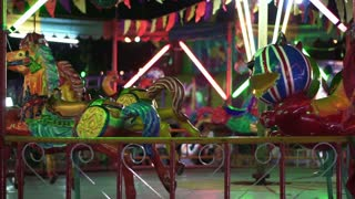 Scary animal carousel in colorful painting. Cheap Asian carnival fair ride