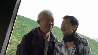 Senior asian couple standing on shop deck looking at mountain and ocean