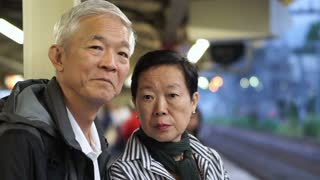 Senior Asian couple taking train transportation together. Having fun on retirement trip around the world together