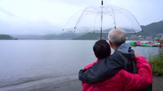 Senior Asian couple under clear umbrella while travel to cloudy lake, explore the world together after retire