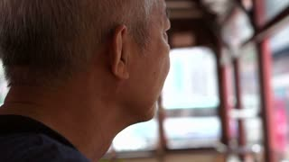 Senior asian man on Hong Kong classic transportation, ding dong, tram.