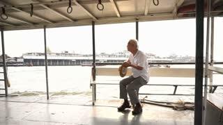 Senior Asian man riding  a ferry boat to cross Chaopraya river in morning sun