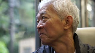 Senior Asian man sitting on train and looking out through window. Thinking and enjoying view during retirement trip