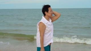 Senior Asian woman smiling next to the ocean