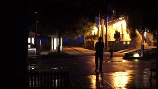 Senior man walking wandering around in the night of city. Wet floor reflects after raining concept of life and loneliness
