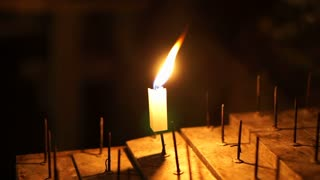 Single candle lit in the dark. Moving flame on sacred stand. Abstract hope and wish