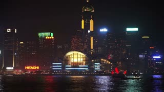 Skyscrapers of Hong Kong. World famous skyline at night with red ancient sail boat