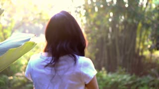 Slow motion Back shot of Asian woman walking in green morning nature