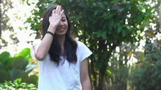 Slow motion mixed race Asian woman smiling in green background nature morning