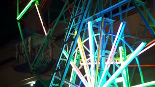 Small old carnival ferris wheel at night illuminate with neon light