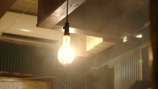 Smoke and lamp light in izakaya restaurant in Tokyo, Japan. Yakiniku, yakitori and other food cooking