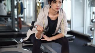 Sporty cool Asian woman training dumbbell lifting at gym