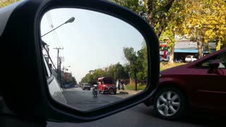 Street view from car side mirror. Let all the cars pass by