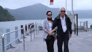 Stylish Asian senior walking together at lake cruise ship pier. Traveling around the world together