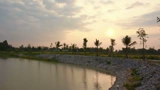 Sunrise at lake, man made water reservoir with rice field and palm trees background