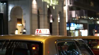 Taxi illuminated sign with city background at night