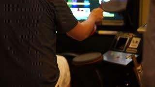 Teen boy playing arcade music game, drum stimulation