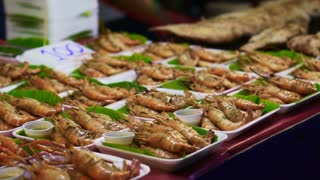 Thailand local street food, grilled prawn and whole fish serve on banana leaves plate