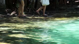 Tourist standing at the edge of emerald pool, turquoise water pond in tropical South East Asia