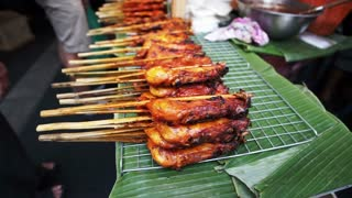 Traditional Thai grilled chicken skewers. Pile of cheap delicious Thai street food selling on banana leaves vendor