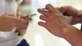 Two people using touchscreen smartphones in public. Close-up of hands typing on two devices. Internet society
