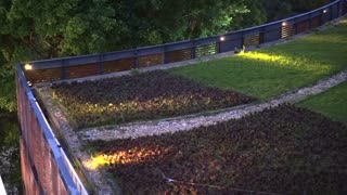 Urban roof garden on the top of building in evening with landscape lighting