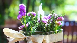 Vase of purple flower and candle with green nature garden background