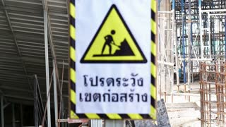 Video A caution construction danger sign in front of blur building site