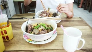 Video Asian girl eating local noodle in Thai restaurant
