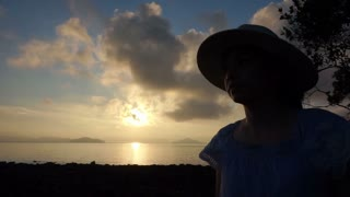 Video Asian girl wearing hat relaxed holiday at golden sunrise ocean beach