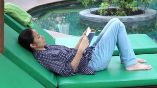 Video Asian woman sits next to the pool and reading book