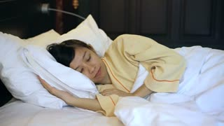 Video Asian woman sleeping tight in bed