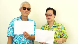 Video Happy Asian senior couple holding white blank sign ready for holiday trip