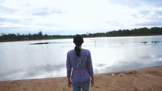 Video of Asian girl stand right next to the lake, sea shore