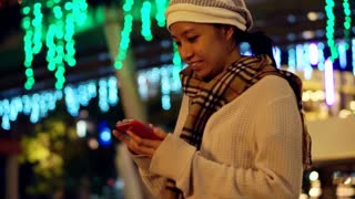 Video of Asian girl using smart phone during holiday season with christmas light background