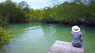 Video of Asian girl wearing hat sits on a small pier next to the Intertidal forest