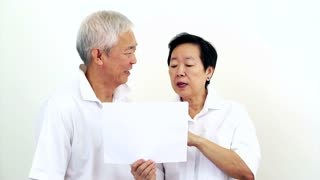 Video of Asian senior couple look at the white sign together. Surprise and happy with the deal on blank white sign