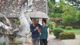 Video of Asian senior couple under umbrella in the rain at the temple