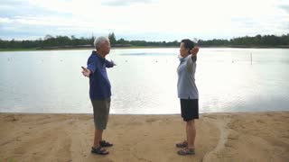 Video of Asian Senior Elderly couple Practice Taichi, Qi Gong exercise outdoor next to the lake