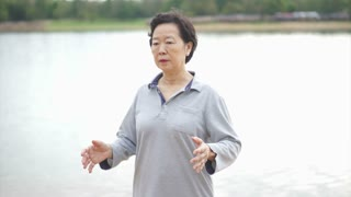 Video of Asian Senior Elderly Practice Taichi, Qi Gong exercise outdoor next to the lake